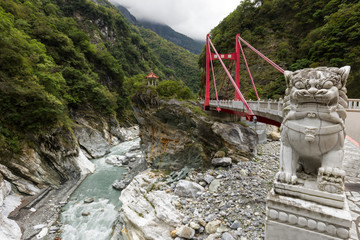 Marble lion statue in front of a red Cimu Bridge at Taroko