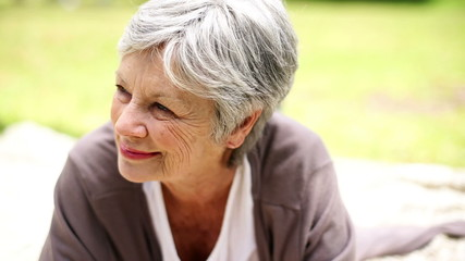 Happy senior woman relaxing in the park thinking