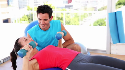 Fit woman lifting dumbbells on blue exercise ball with trainer