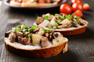 Delicious bruschetta with mushrooms on table close-up