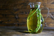 Essential Oil with rosemary in glass jug, on wooden background