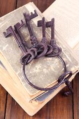 Old keys on old books on wooden background