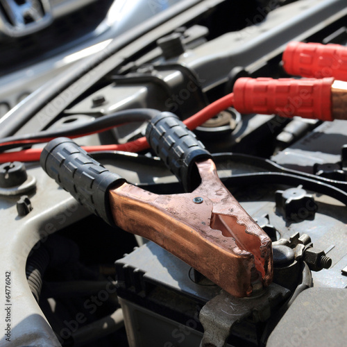 Charging battery car with electricity trough jumper cables - 64776042