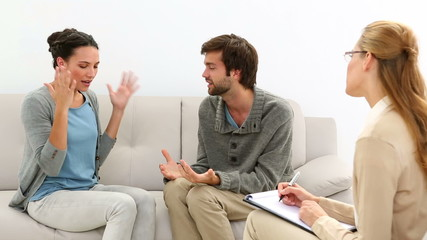 Young couple arguing while therapist takes notes