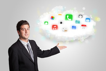 Young man presenting cloud with colorful app icons and symbols