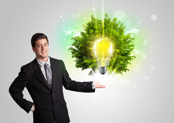Young man presenting idea light bulb with green tree