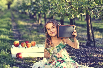 Girl in apple orchard with a plate for your text