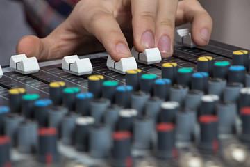 Fingers operating sound console