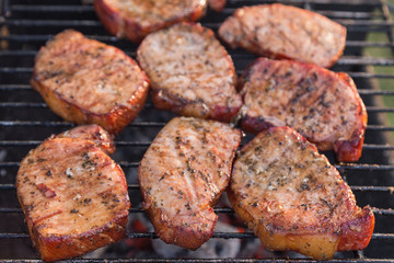 Thick seasoned pork chops cooking on the grill