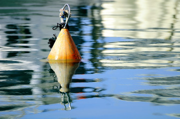 Buoy floating on water surface in old Jaffa port. Israel.