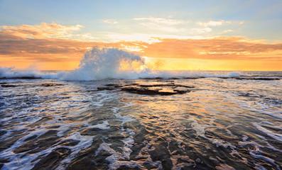 Sunrise seascape splash in the shape of a wave