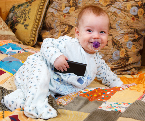 Funny baby with dummy and cell phone in his hand