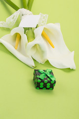 gift and white lilly flowers on green with label