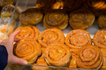 hand hold yeast bun with cinnamon in store