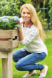 Hübsche blonde Frau mit Blumen im Garten