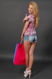 Junge Frau mit Einkaufstaschen und Daumen hoch.
