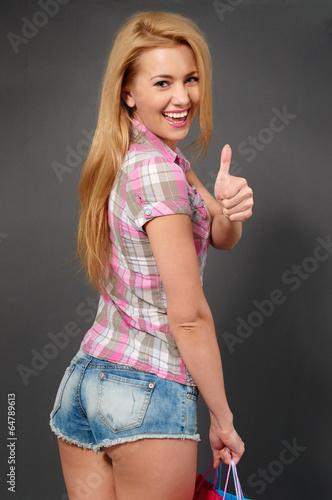 Junge Frau beim Shoppen mit Daumen nach oben.