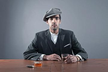 Mafia fashion man wearing grey striped suit with cap. Sitting at