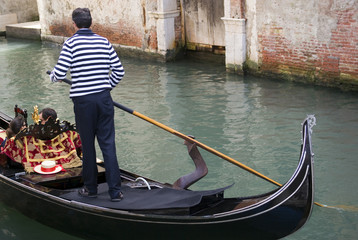 Gondolier are boating tourists in the typical venetian gondola