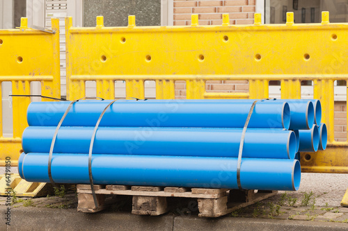 Blaue Rohre aus Kunststoff vor gelben Absperrbaken