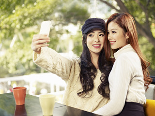 young women taking selfie in cafe