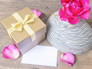 Gold gift box with card and rose in vase