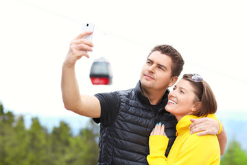Young couple taking pictures in mountains