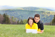 Young couple and laptop in the mountains