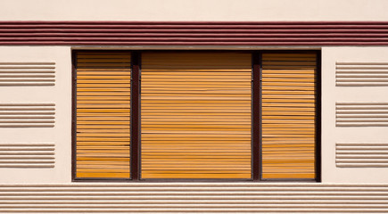 Closed window with brown wooden shutters
