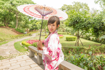 Chinese woman wearing a yukata in Japanese style garden holding