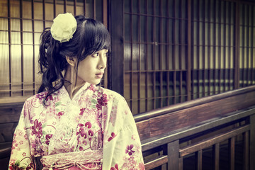 Asian woman wearing a yukata in front of Japanese style windows;