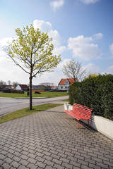 Rastplatz mit roter Bank im Dorf