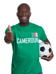 Soccer fan from Cameroon with football showing thumb up