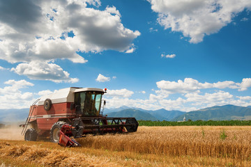 A red harvester in work with mountains in background