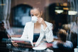 Young businesswoman drinking coffee and using tablet computer in