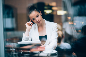 Pensive young businesswoman using tablet computer in cafe