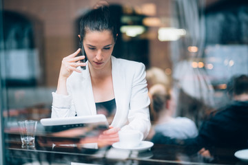 Young businesswoman talking on the phone in coffee shop