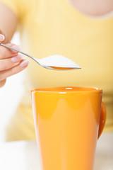 Woman sweetening drink