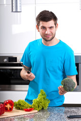 Man with broccoli and knife in hands