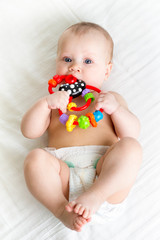 baby girl lying on back weared diaper with teethers