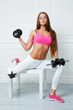 A young fit girl holding two dumbbells