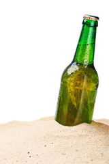 Beer bottle on a sandy beach isolated