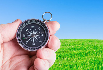 compass in hand on nature background