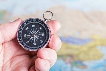 compass in hand over travel map