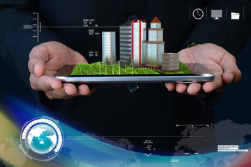 Man holding a cityscape in tablet computer