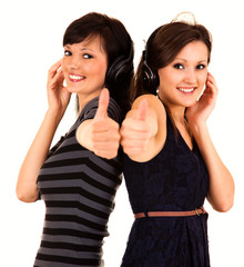two girl friends in heaphones with thumbs up
