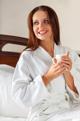 smiling woman in bedroom drinking coffee on bed
