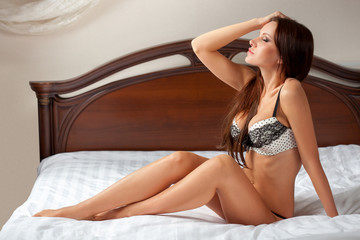 woman sitting on headboard of bed