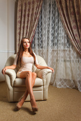 beautiful woman sitting on white leather lounge