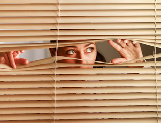 Portrait of a woman looking through out the blinds